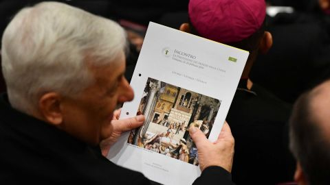 A cardinal holds the liturgy booklet during the opening of the Vatican meeting.