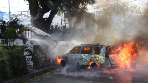 Firefighters extinguish burning cars at the offices of Haiti's state television station on February 13.