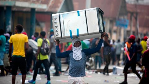 A man carries a cooking stove during clashes in Port-au-Prince on Tuesday, February 12.