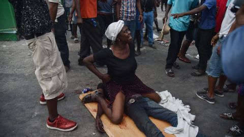 A mother cries while sitting on the body of her dead son who was shot during clashes in Port-au-Prince on February 9.