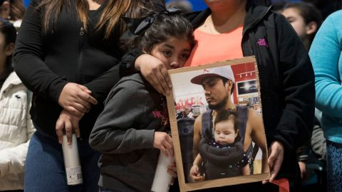 Esmeralda Bautista stands at a vigil last year with a photograph of her brother Luis Bautista-Martinez, one of the workers detained when ICE raided a Tennessee meatpacking plant.