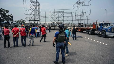 Workers prepare for a rival concert on the Venezuelan side of the bridge as a member of the country's intelligence service looks on.