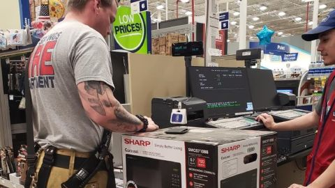 Firefighter Doug Hope buys a microwave for an elderly woman in High Springs, Florida, after his crew responded to a false alarm at her residence.