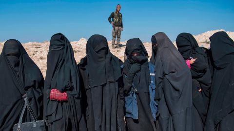 A fighter with the US-backed Syrian Democratic Forces keeps watch near veiled women after they fled from the Baghouz area in eastern Syria on February 12, 2019 during an operation to expel hundreds of ISIS jihadists from the region.