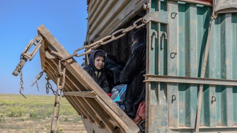 A truck carrying children on February 20, 2019, as a convoy of vehicles believed to be surrendering ISIS members is escorted by SDF fighters out of Baghouz.