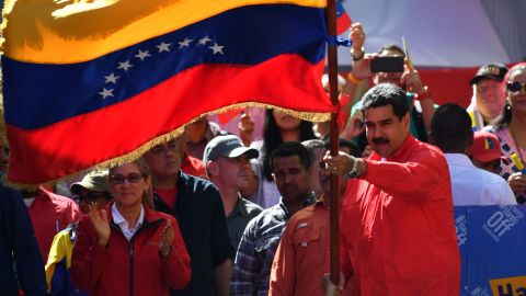 Maduro waves the national flag during a pro-government march in Caracas on February 23. During the rally at the Venezuelan capital, Maduro told supporters he is breaking all diplomatic relations with Colombia and is calling for its ambassadors and consuls to leave Venezuela. Maduro recently began a second term after a 2018 vote that his political opposition and many in the international community denounced as a sham.