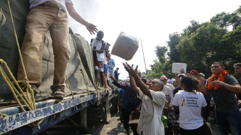 People attempt to salvage packages from a truck loaded with humanitarian aid after it was set ablaze on a bridge between Cucuta, Colombia, and Urena, Venezuela, on February 23.