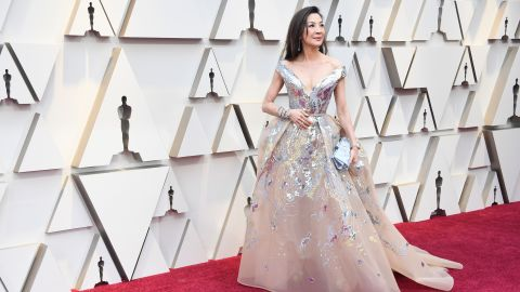 """The """"Crazy Rich Asians"""" star Michelle Yeoh has worn Elie Saab to numerous red carpets this year. This time, she paired a shimmery, off-shoulder gown with a showstopping bracelet by Chopard and watch by Richard Mille."""