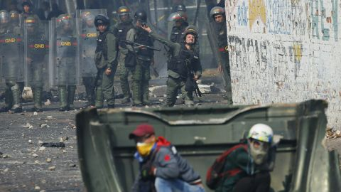 A Venezuelan Bolivarian National Guard officer throws a teargas grenade towards demonstrator in Urena Saturday.