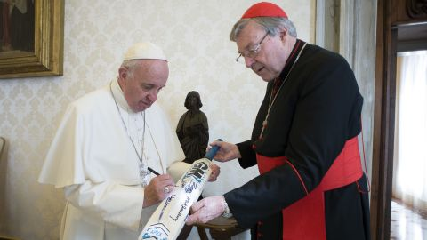 Pope Francis signs a cricket bat he received from Cardinal George Pell, at the Vatican Thursday, Oct. 29, 2015. Pope Francis has received an unusual gift aimed at boosting relations between the Catholic and Anglican churches: A cricket bat signed by the Archbishop of Canterbury and his team following their recent rematch with the Vatican's XI on Rome's Campanelle grounds. Australian Cardinal George Pell, a former rugby player who nevertheless knows cricket, gave Francis the bat Thursday after the St. Peter's Cricket Club beat the Church of England's XI by 43 runs in a 20-over match this weekend. (L'Osservatore Romano/Pool Photo via AP)