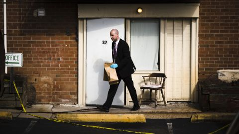 """An investigator carries out items from the Robert Morris Apartments in Morrisville, Pa., Tuesday, Feb. 26, 2019. A mother and her daughter killed five of their close relatives, including three children, and were found """"disoriented"""" after child welfare authorities arrived for a surprise visit at their chaotic suburban Philadelphia apartment, police and prosecutors said Tuesday. (AP Photo/Matt Rourke)"""