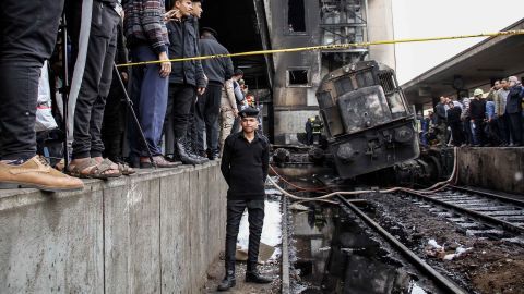 A policeman stands next to wreckage on the tracks after the accident at the Cairo train station.