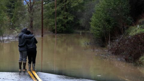 Ari Herman, left, and Lea Herman eye a flooded section of a highway Wednesday in Guerneville.