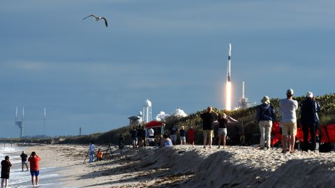 People watch from Playalinda Beach at Canaveral National Seashore as a SpaceX Falcon 9 rocket successfully launches carrying the Es'hail-2 communications satellite for the country of Qatar on November 15, 2018 from pad 39A at the Kennedy Space Center in Florida, US.