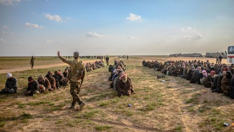 Men suspected of being ISIS fighters wait to be searched by SDF members after leaving Baghouz.