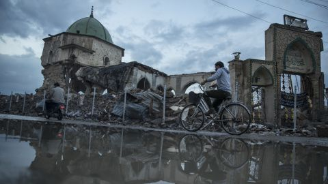 A resident rides a bicycle past the Al Nouri Mosque in the Old City of Mosul, Iraq, on Monday, Nov. 5, 2018. More than a year after the brutal fighting that liberated the city ended, and a devastating air campaign that mostly flattened it, much of Mosul lies in ruins. Few residents have returned and there is little commercial activity other than the destruction of devastated buildings and scavenging for metal. Photographer: Victor J. Blue/Bloomberg via Getty Images