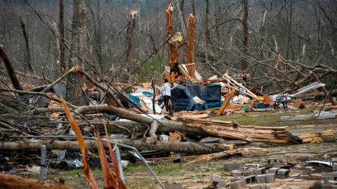 Brittney Downs looks through the debris of a family member's destroyed home the day after a deadly tornado ravaged the area, in Beauregard, Ala., Monday, March 4, 2019. (AP Photo/Julie Bennett)