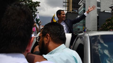 Venezuelan opposition leader and self-proclaimed acting president Juan Guaido greets supporters upon his arrival in Caracas on March 4, 2019. - Venezuela's opposition leader Juan Guaido was mobbed by supporters, media and the ambassadors of allied countries as he returned to Caracas on Monday, defying the threat of arrest from embattled President Nicolas Maduro's regime. Just before his arrival, US Vice President Mike Pence sent a warning to Maduro to ensure Guaido's safety. (Photo by Yuri CORTEZ / AFP)        (Photo credit should read YURI CORTEZ/AFP/Getty Images)
