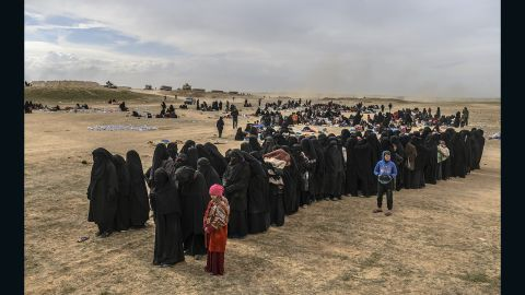 Civilians evacuated from the embattled holdout of Baghouz wait to be screened by SDF fighters.