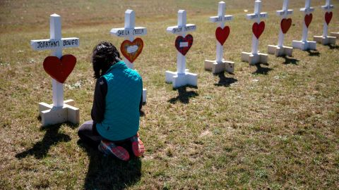Jessica Taylor prays in front of a cross for Jonathan Bowen, 9, at a makeshift memorial for the victims of a tornado in Beauregard, Ala., Wednesday, March 6, 2019.
