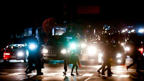 Residents cross a street in the dark after a power outage in Caracas, Venezuela, Thursday, March 7, 2019. A power outage left much of Venezuela in the dark early Thursday evening in what appeared to be one of the largest blackouts yet in a country where power failures have become increasingly common. Crowds of commuters in capital city Caracas were walking home after metro service ground to a halt and traffic snarled as cars struggled to navigate intersections where stoplights were out. (AP Photo/Eduardo Verdugo)