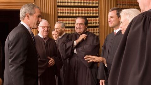 Bush enjoys a light moment with Roberts and other Supreme Court justices on Roberts' first day. With Bush, from left, are John Paul Stevens, Ruth Bader Ginsburg, David Souter, Antonin Scalia, Roberts, O'Connor and Kennedy.