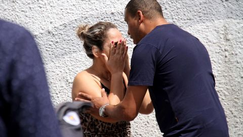A man comforts a woman at the Raul Brasil State School in Suzano, Brazil, Wednesday, March 13, 2019. The state government of Sao Paulo said two teenagers, armed with guns and wearing hoods, entered the school and began shooting at students. They then killed themselves, according to the statement. (Mauricio Sumiya/Futura Press via AP)