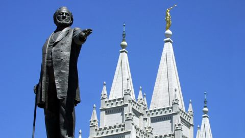A statue of Brigham Young, second president of the Church of Jesus Christ of Latter Day Saints, stands in the center of Salt Lake City with the Mormon Temple spires in the background in 2001.