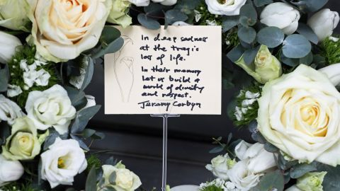 """This wreath was placed by Labour Party leader Jeremy Corbyn outside the New Zealand High Commission in London. """"In their memory, let us build a world of dignity and respect,"""" he said on the note."""