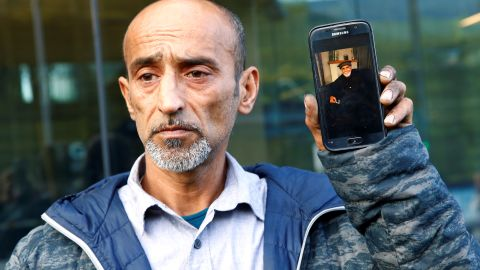 Omar Nabi holds up a phone displaying a photo of his dead father Haji Daoud, at the district court in Christchurch.
