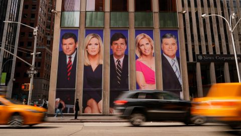 Traffic on Sixth Avenue passes by advertisements featuring Fox News personalities, including Bret Baier, Martha MacCallum, Tucker Carlson, Laura Ingraham, and Sean Hannity, adorn the front of the News Corporation building.