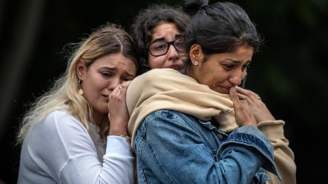 Women weep as they comfort each other during a vigil near the Masjid Al Noor mosque in Christchurch, New Zealand, on Monday, March 18.