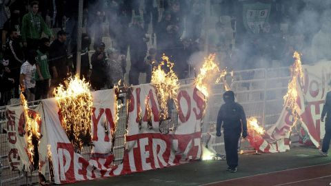 Fans burn a banner in front of the stands during the game, which was ultimately abandoned after 70 minutes due to persistent crowd trouble.