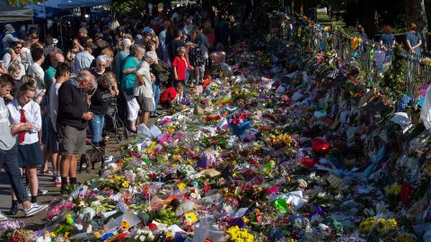 """Floral tributes to those who were gunned down at the two mosques are seen against a wall bordering the Botanical Garden in Christchurch on March 19, 2019. New Zealand Prime Minister Jacinda Ardern vowed never to utter the name of the gunman as she opened a sombre session of parliament with an evocative """"as-salaam alaikum"""" message of peace to Muslims."""