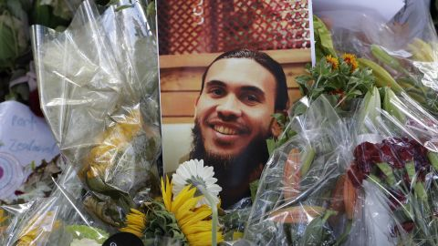 A photo tribute for Christchurch mosque shooting victim Tariq Omar lies amid mounds of flowers across the road from the Al Noor mosque in Christchurch, New Zealand Tuesday, March 19.