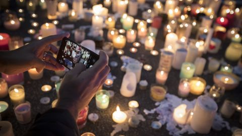 A mourner takes a picture of candles commemorating victims of Friday's shooting, outside the Al Noor mosque in Christchurch, New Zealand, Monday, March 18. Three days after the attack, New Zealand's deadliest shooting in modern history, relatives were anxiously waiting for word on when they can bury their loved ones.