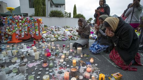 People mourn at a makeshift memorial site near the Al Noor mosque in Christchurch, New Zealand, on Tuesday, March 19. Streets near the hospital that had been closed for four days reopened to traffic as relatives and friends of the victims of last week's mass shootings continued to stream in from around the world.