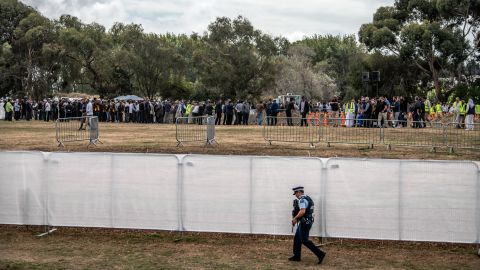 An armed policeman walks alongside a fence at Memorial Park Cemetery as a funeral takes place for two of the victims of the Christchurch attack on March 20 in Christchurch.