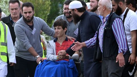 """Zaid Mustafa (in wheelchair), who was wounded in the attack on two mosques in Christchurch, New Zealand, <a href=""""https://www.cnn.com/2019/03/20/australia/new-zealand-victims-funerals-christchurch-intl/index.html"""" target=""""_blank"""">attends the funeral</a> of his slain father, Khalid Mustafa and brother Hamza Mustafa at the Memorial Park Cemetery in Christchurch on March 20."""