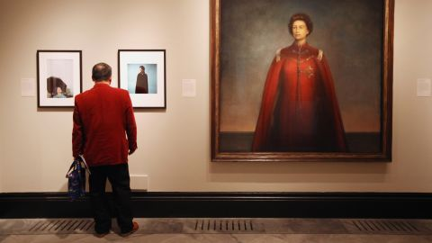 LONDON, ENGLAND - MAY 16:  A man views images of Her Majesty Queen Elizabeth II inculding one by artist Pietro Annigoni entitled 'Queen Elizabeth II' (R) in the National Portrait Gallery's exhibition 'The Queen: Art & Image' on May 16, 2012 in London, England. The exhibition, which opens to the public on May 17, 2012 and runs until October 21, 2012, features a wide-ranging display of images of The Queen from throughout her 60 year reign.  (Photo by Oli Scarff/Getty Images)