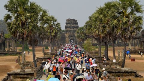 <strong>Siem Reap, Cambodia:</strong> Crowds of tourists shield themselves from the sun on a warm day at the sprawling Angkor Wat temple, believed to be the largest religious monument in the world.