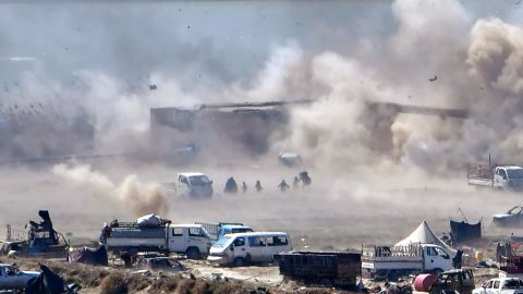 TOPSHOT - People are seen fleeing as heavy smoke rises above the Islamic State (IS) group's last remaining position in the village of Baghouz during battles with the Syrian Democratic Forces (SDF), in the countryside of the eastern Syrian province of Deir Ezzor on March 18, 2019. - A shroud of black smoke covered the Islamic State group's last Syria redoubt today as US-backed forces battled holdout jihadists after a night of shelling and heavy air strikes. The Kurdish-led SDF have been closing in on IS fighters holed up in a small sliver of territory in the village of Baghouz in eastern Syria since January. (Photo by GIUSEPPE CACACE / AFP)        (Photo credit should read GIUSEPPE CACACE/AFP/Getty Images)