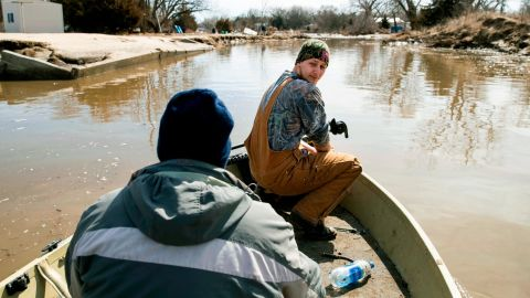 Helmut Shea Kaukver III and Tim Rockford return to their neighborhood in Bellwood, Neb.,  which was only accessible by boat because of floodwaters.