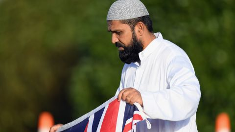 A mourner holds a New Zealand flag during a mass burial at Memorial Park Cemetery in Christchurch on March 22.
