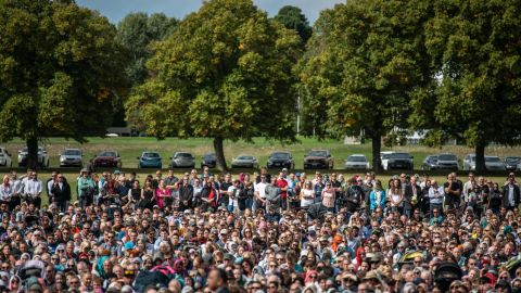 Visitors look on as Muslims attend Friday prayers in a park near Al Noor mosque in Christchurch, New Zealand.