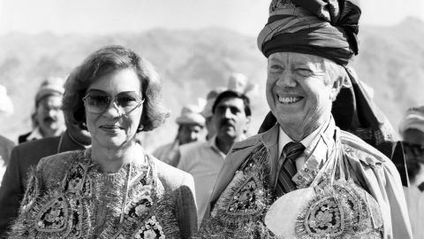 The Carters wear glittering garlands and a turban given to them by Pakistani tribesmen at the Pakistan-Afghanistan border in November 1986. They also received a pair of rams.