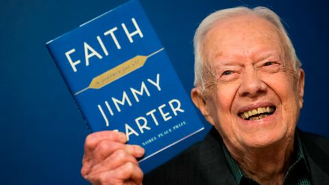 """Carter holds up a copy of his new book """"Faith: A Journey For All"""" at a book-signing event in New York in March 2018."""