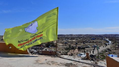 The SDF flag flutters atop a building in Baghouz.