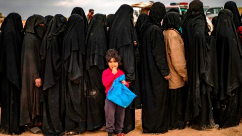 TOPSHOT - Fully-veiled women and children queue at a screening point as hundreds of civilians, who streamed out of the Islamic State group's last Syrian stronghold, arrive in an area run by US-backed Syrian Democratic Forces outside Baghouz in the eastern Syrian Deir Ezzor province on March 5, 2019. - Shell-shocked and dishevelled, hundreds of women and children stumbled through eastern Syria's windswept desert carrying what little they could after fleeing the IS group's final speck of territory. (Photo by Delil SOULEIMAN / AFP)        (Photo credit should read DELIL SOULEIMAN/AFP/Getty Images)