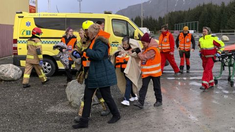 Rescued passengers are helped from a helicopter.